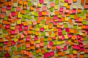 Lots of different colored post-its on a wall.