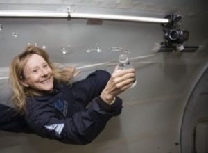 Picture of Esther Dyson floating in zero gravity holding an open bottle of water that is leaking out.