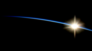 View of distant sun rising over blue edge of Earth.
