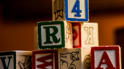 A stack of wooden building blocks with letters, numbers and pictures.