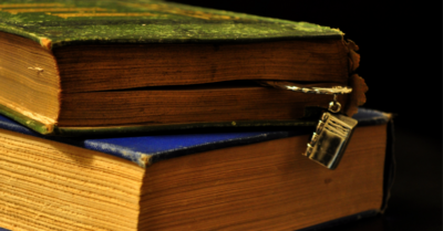 Two old books seen from the side: One with a green cover and a metal bookmark stacked slightly ajar on one with a blue cover. Image credit: Old Books (https://flic.kr/p/9ot8E8) by Zan Ready, licensed CC BY-SA (https://creativecommons.org/licenses/by-sa/2.0/).