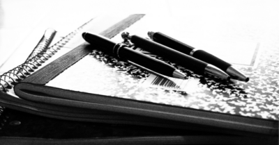 A black and white photo of three dark ballpoint pens lying diagonally on top of a mottled composition book on top of some other books. Image credit: Three Pens on a Composition Book (https://flic.kr/p/oEFEGs) by Leslie Richards, licensed CC BY (https://creativecommons.org/licenses/by/2.0/).