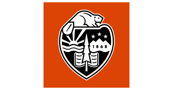 Oregon State University logo with a black and white shield on a tomato-red background and the following in the seal: beaver, sun, ocean, evergreen tree, book mountains with stars over them and the year 1868 in the mountains